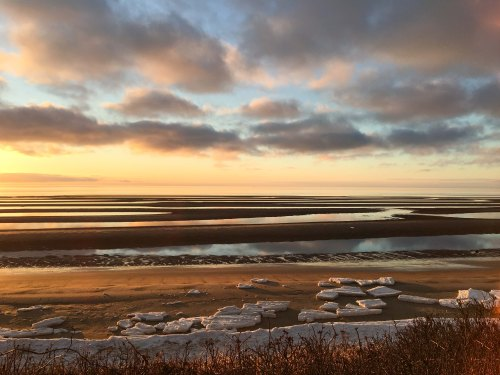 A winter sunset at First Encounter Beach, Cape Cod Massachusetts. Chunks of ice are scattered on the beach, with a row of snow where the tide withdrew; reflections of pink-edged clouds are seen in the water of the flats.
